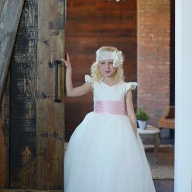 A girl standing by a wooden door wearing an ivory made to measure flower girl dress with a sweetheart neckline, very full tulle skirt and a wide silk pink sash.