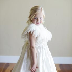 A young flower girl at a wedding wearing an ivory feathered cape and an ivory flower girl dress.