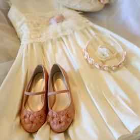 An ivory flower girl dress with lace sash and blush pink flower together with pink flower girl shoes and a flower girl headband.