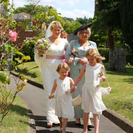 A bride and bridesmaid with two flower girls wearing an ivory lace flower girl dress with a blush pink flower. These flower girl dresses are handmade to measure in London, UK.