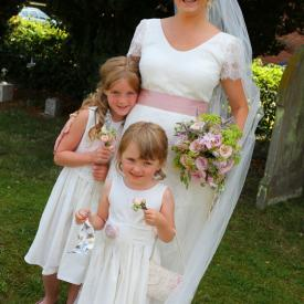A bride with her flower girls standing in a garden. The bride is wearing an ivory wedding dress and the flower girls are wearing an ivory flower girl dress with a lace belt. These flower girl dresses are handmade to measure in London, UK.
