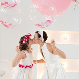 A bride and a flower girl wearing white silk dresses with pink flowers and holding pink balloons.