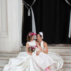 A bride sitting on the steps at a church with a 10 year old flower girl on her knee. The flower girl is wearing a white silk dress with pink flowers.
