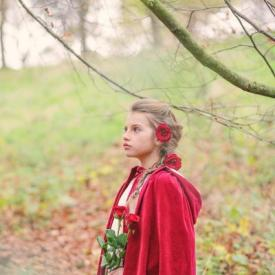 A flower girl standing in a forest with a red cape with a hood.