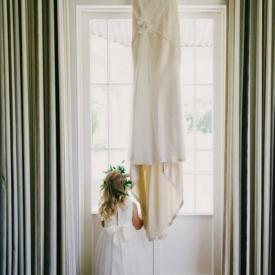 A flower girl standing at a window wearing an ivory flow girl dress with a big peony flower on the shoulder.