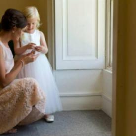 A flower girl and bridesmaid wearing ivory silk dresses with a tulle skirt and peony flower.