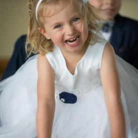 A flower girl sitting under a table wearing her handmade white and navy blue flower girl dress with navy silk flower and tulle skirt.
