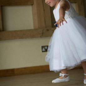 A  young flower girl in a white and navy blue dress with tulle skirt and navy silk flower.