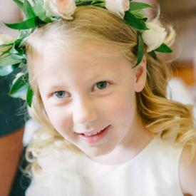 A flower girl wearing an green and ivory flower girl wreath.