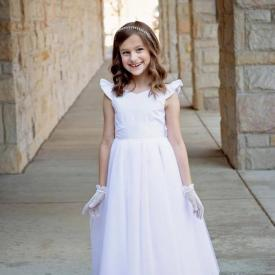A girl standing at a church in a white silk first communion dress and white gloves.
