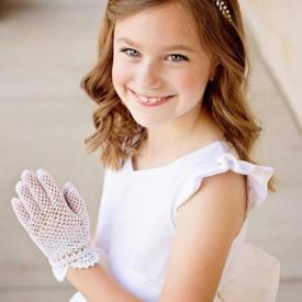 A girl at her first communion with her hands together wearing white gloves and a silk flower girl dress with a tulle skirt.