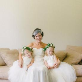 A bride with her two flower girls wearing ivory flower girl dresses with a tulle skirt.