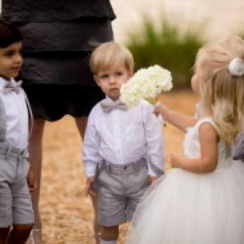 A girl wearing an ivory flower girl dress and two pageboys in tweed with bow ties.