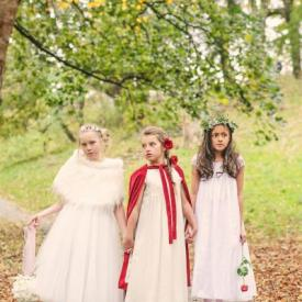 Three young flower girls wearing handmade dresses in ivory with a feather shawl and a red cape.