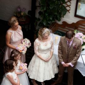 A bride wearing an ivory 1950s style wedding dress with a group of flower girls wearing ivory and pink flower girl dresses with pink roses.
