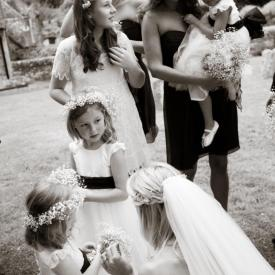 A bride with her flower girls at a wedding wearing a white flower girl dress made in the UK with a navy sash.
