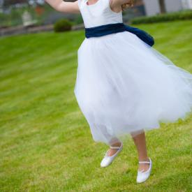 A 5 year old flower girl jumping on the grass wearing a white flower girl dress with lace sleeves and a navy blue sash.