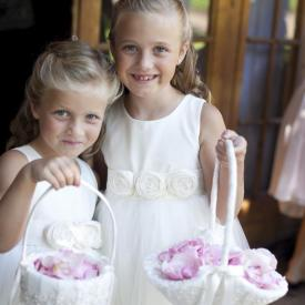 Two flower girls wearing ivory cotton flower girl dresses with roses on the sash and carrying pink flowers in a basket