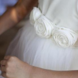 A close up of a flower girl dress in ivory with  a tulle skirt and rolled rosettes on the front.
