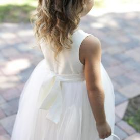 A flower girl wearing an ivory flower girl dress in cotton with a tulle skirt and carrying a flower girl basket.