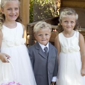 Two flower girls in ivory flower girl dresses with a tulle skirt and roses on the belt. The pageboy has a boys pre-tied bow ties and wears a suit.
