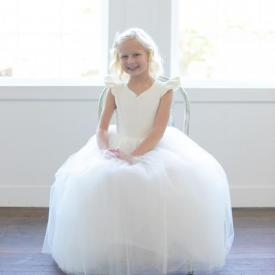 A 6 year old flower girl wearing an ivory and white flower girl dress with a full skirt and a sweetheart neckline. Made in London, UK.