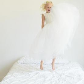 A flower girl bouncing on a bed showing her full tulle flower girl skirt in ivory. The flower girl dress is in ivory and has a cotton bodice with a sweetheart neckline and a big bow.