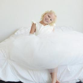 A toddler flower girl sitting on a bed wearing an ivory  flower girl dress which has a full tulle skirt and a sweetheart neckline. Made in London, UK.