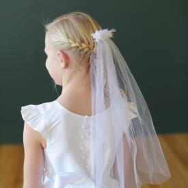 A young girl wearing a first holy communion dress in white silk with a tulle skirt and diamante. The girl is also wearing a first communion veil in white with flowers.