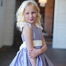 A flower girl and junior bridesmaid wearing a purple silk flower girl dress with an ivory sash and lace sleeves.