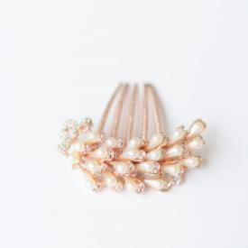 A bride at a wedding wearing a pearl bridal hair comb in rose gold.The pearls sweep across the comb in a vintage deco style.