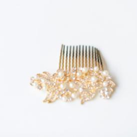 A bride wearing a gold coloured pearl and diamante bridal hair comb.