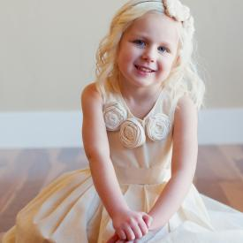 A toddler flower girl sitting on the floor wearing an ivory toddler flower girl dres with pretty roses around the collar and a wide satin belt handmade in the UK.