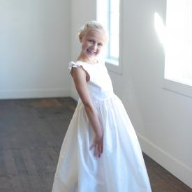 A young girl wearing a white satin first communion dress with a lace hem and there is a flower with  diamante at the waist of the dress.