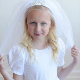 A girl wearing a first communion dress in white with a doubl elayer tulle veil and a beaded headband