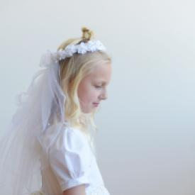 A pretty, white first communion veil and hair crown with a double layer of tulle and delicate white flowers on the crown