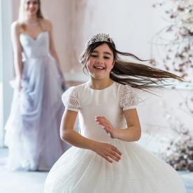 A 9 year old flower girl wearing a white and ivory flower girl dress with a full lace skirt and lace puff sleeves.