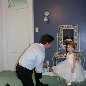 A groom kneeling in front of a toddler flower girl wearing a designer ivory flower girl dress with a lace sash and a blush pink flower. These flower girl dresses are handmade to measure in London, UK.