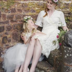 A bride and a flower girl wearing an ivory flower girl dress and a knee length ivory wedding dress.