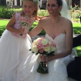 A bride sitting on a wall with her flower girl. The bride is wearing an ivory wedding dress and the flower girl dress has a pink bodice and an ivory tulle skirt with flowers on the belt. These flower girl dresses are handmade to measure in London, UK.