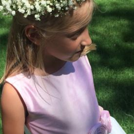 A flower girl at a wedding wearing an ivory tulle flower girl dress with a pink bodice and pink flowers on the sash. These flower girl dresses are handmade to measure in London, UK.