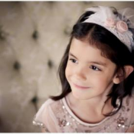 A girl at a wedding wearing a lace flower girl headband with blush pink flower.