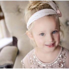 A young flower girl at a wedding wearing a lace headband with a blush pink flower.