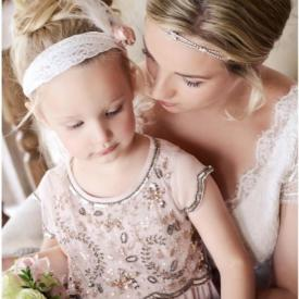 A bride and a flower girl wearing a pink flower girl dress with a lace headband and a blush pink flower.