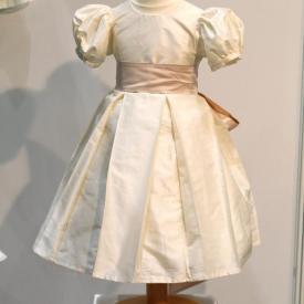 A silk flower girl dress or junior bridesmaid dress with puff sleeves and a wide silk sash with a big bow.
