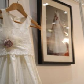 A flower girl dress on a hanger in cotton with a lace sash and a pure silk blush pink flower with feathers.