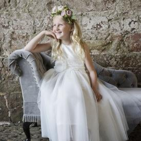 A flower girl sitting on a bench and wearing an ivory silk and tulle flower girl dress.