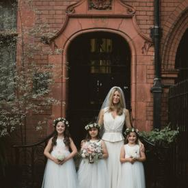 A bride standing outside a church with three toddler flower girls who are wearing ivory tulle dresses with pink and sherbet lemon sashes.