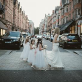 A bride and three toddler flower girls walking across a London street. The flower girls are wearing ivory flower girl dresses with sherbet lemon and pink sashes.