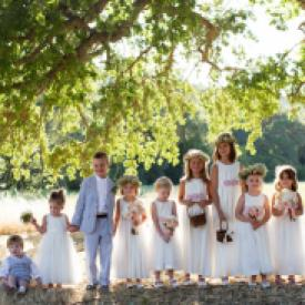 A lage  group of flower girls and pageboys wearing a cotton flower girl dress with tulle skirt and blush pink flowers on the sash.
